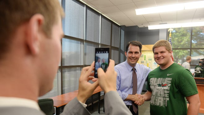 Gov. Scott Walker has his photo taken with members of a group of UW-Green Bay students in Mary Ann Cofrin Hall.