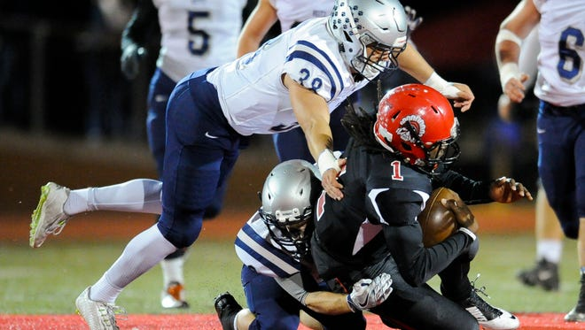 Reitz's Connor Deweese (2) and Reitz's Joey Diekmann (38) tackle Harrison's David Felton (1) during the Class 4A Sectional 24 football championship game at Romain Stadium, Friday, Nov, 4, 2016.
