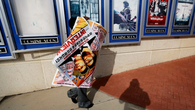 """A poster for the movie """"The Interview"""" is carried away by a worker after being pulled from a display case at a Carmike Cinemas movie theater in Atlanta."""