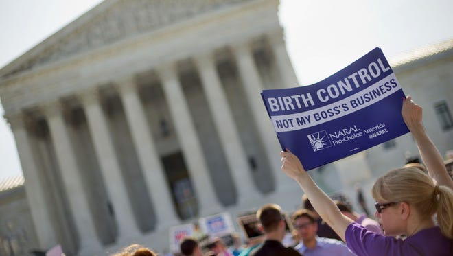 FILE - This June 30, 2014 file photo shows a demonstrator holding up a sign outside the Supreme Court in Washington on the day the court decided in the Hobby Lobby case to relieve businesses with religious objections of their obligation to pay for women's contraceptives among a range of preventive services the new health law calls for in their health plans. How much distance from an immoral act is enough is the difficult question behind the next legal dispute over religion, birth control and the new health law that is likely to be resolved by the Supreme Court. The issue in more than four dozen lawsuits from faith-affiliated charities, colleges and hospitals who oppose some or all contraception as immoral is how far the Obama administration must go to accommodate them.  (AP Photo/Pablo Martinez Monsivais, File)