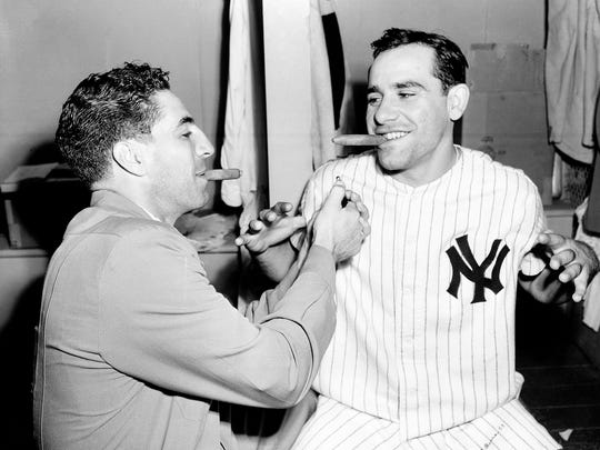 In this Sept. 25, 1951 photo, New York Yankees catcher Yogi Berra, right, accepts a light from Yankees shortstop Phil Rizzuto after Berra handed out cigars to celebrate the birth of his son in the Yankees clubhouse in New York.
