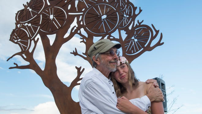 John Franzen comforts his granddaughter Lily Brooks, daughter of Shawn Brooks, during a dedication ceremony for a memorial on the Spring Creek Trail to honor her father who committed suicide four years ago Thursday, August 13, 2015. The memorial ceremony to honor the former owner of The Cycologist bike shop featured music and stories about Shawn.