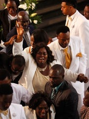 Delina Lubin, center, grieves for her son Sean Archilles as his casket is carried out following his funeral on Saturday at CityGate Ministries in Fort Myers.