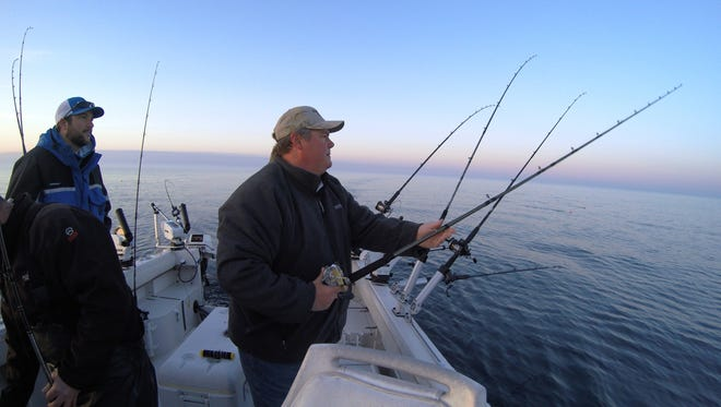 Jim Frazer sets his rods during an early morning salmon fishing trip