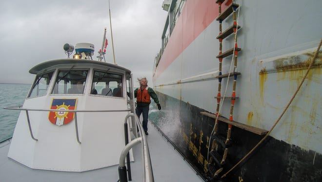 Wayne Jurs, of Port Huron, moves to attach the pilots' bags to a line so the crew can haul them up the side of the freighter, Wednesday, April 6 in Lake Huron.