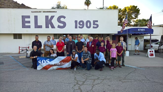 Caption: Marines and SOS Volunteers in front of a 1960 Lincoln Continental Mark IV at their recent Car Show fundraiser.