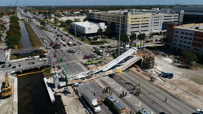 This March 15, 2018 file photo shows the main span of the a pedestrian bridge after it collapsed over several cars causing fatalities and injuries. Documents obtained by The Associated Press through a public records request show that the Florida Department of Transportation in October 2016 ordered Florida International University and its contractors to move the bridge's main, signature pylon 11 feet north to the edge of a canal, widening the distance the crossing would gap between its supports and requiring a new base structural design.