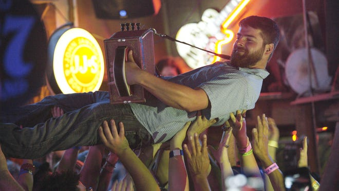 "Accordionist Ervin Frey enjoys some crowd-surfing during a performance at the Blue Moon Saloon in the film, ""Roots of Fire."""
