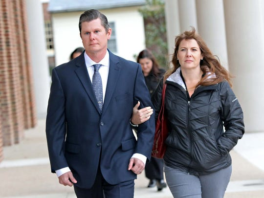 Dover police Cpl. Thomas Webster walks with his wife, Suzanne, into Kent County Courthouse on Nov. 29. Webster was accused of kicking a suspect in the head during an arrest. The terms of a settlement regarding the case have not been released.