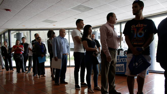 In this Tuesday, July 19, 2016, photo, people stand in line to register for a job fair, in Miami Lakes, Fla. On Tuesday, Sept. 20, 2016, the Labor Department reports on state unemployment rates for August.