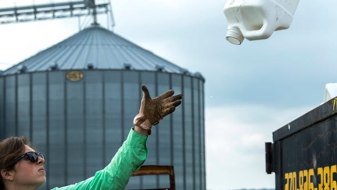 Camille Lambert, Henderson County's agriculture agent, tosses empty plastic jugs into a recycling dumpster during the annual Chemical Rinse and Return Jug Day at Scott Farms near Zion, Ky., Tuesday morning.
