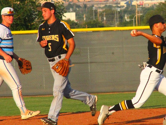 Alamogordo's Josh Caraway, 5, and teammate Alex Ramirez, far right, turn a double play during infield practice prior to the game on Friday.