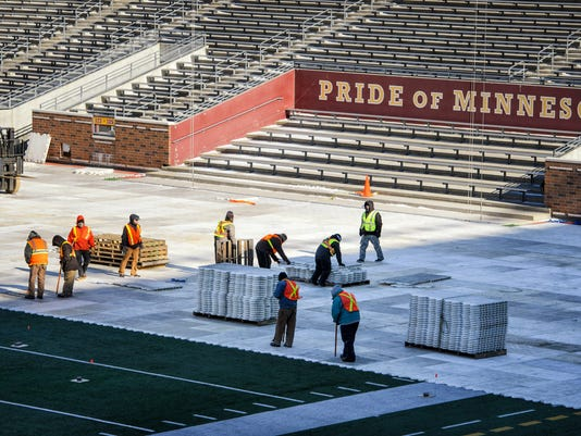 Workers begin laying down the first pieces of flooring  to transform TCF Bank Stadium from a football field to a hockey rink Tuesday, Feb. 9, 2016, in Minneapolis, for the NHL Stadium Series to be held Feb. 20-21.   (Glen Stubbe/Star Tribune via AP)