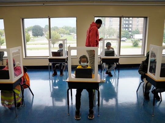 Paraprofessional Jaevon Walton reminds a student to wear his face mask in a learning pod of second through seventh graders at Harvest Best Academy on Tuesday in Minneapolis.