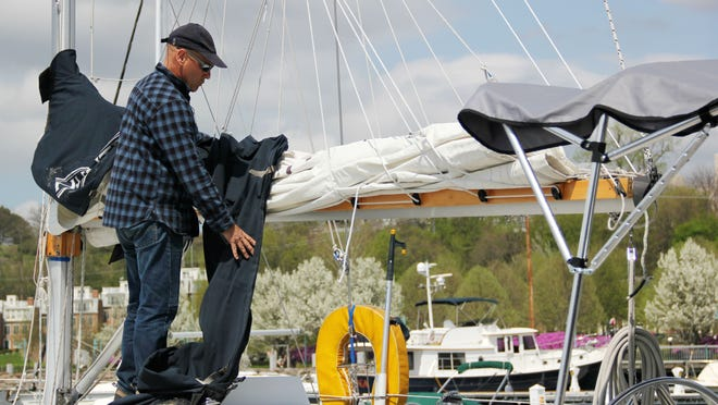 """Gideon Bavly of Burlington works on his boat """"Let's Go Sailing"""" at the Boathouse dock during its opening day Thursday. Bavly said he docks at the Boathouse each year and gives rides around Lake Champlain to customers."""