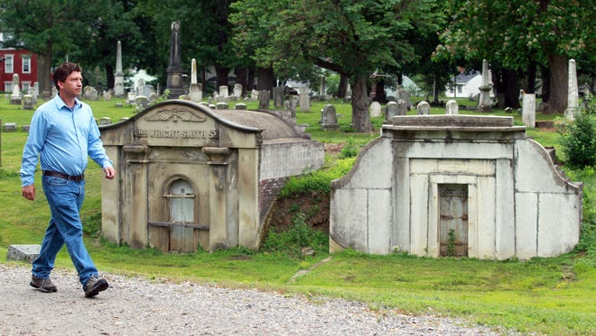 Gary Davidson, superintendent of Linden Grove Cemetery, Covington, walks along a road past mausoleums in the cemetery. The cemetery was founded in 1843.