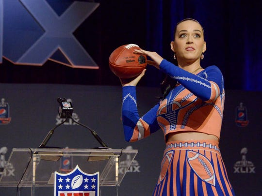 Recording artist Katy Perry throws a football during the Super Bowl XLIX halftime show press conference at the Phoenix Convention Center Jan. 29.
