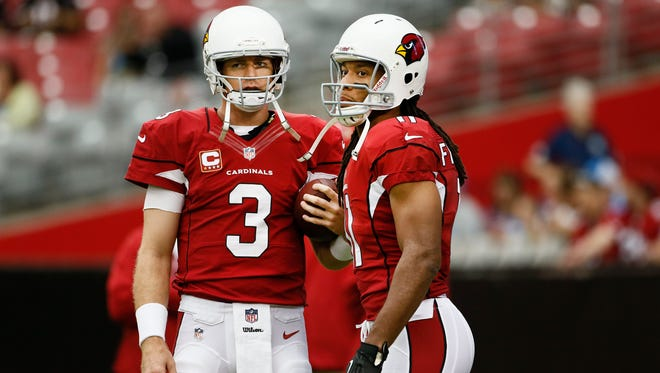 Carson Palmer talks to wide receiver Larry Fitzgerald against the Detroit Lions on Sunday, Sept. 15, 2013 at University of Phoenix Stadium in Glendale, Ariz.