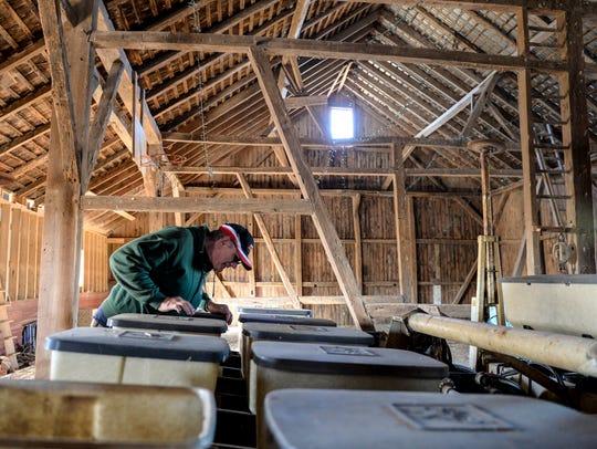Lynn Struphar checks a corn seeder at his farm along