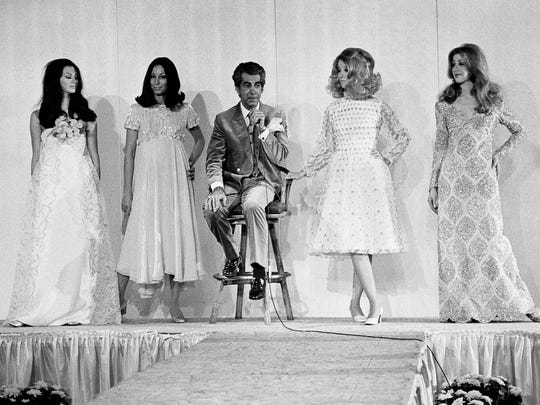 Designer Mr. Blackwell is surrounded by models as he