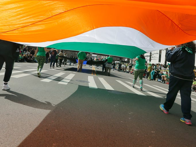 A large Irish flag is carried during the St. Patrick's