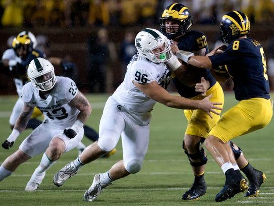 Michigan State's Jacob Panasiuk, left, pressures Michigan