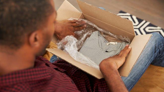 Man opening clothing purchase