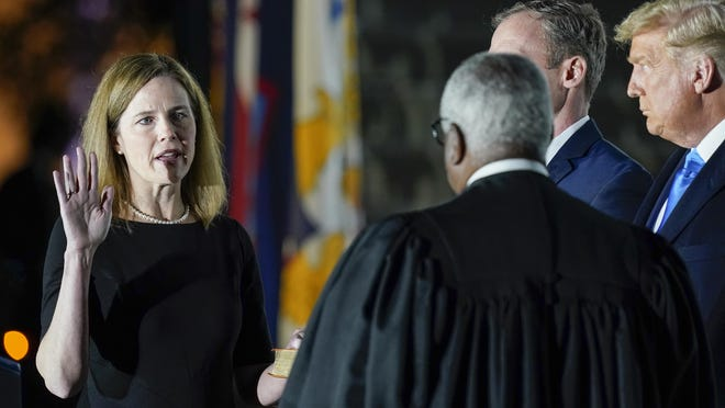 President Donald Trump watches as Supreme Court Justice Clarence Thomas administers the Constitutional Oath to Amy Coney Barrett on the South Lawn of the White House White House in Washington, Monday, Oct. 26, 2020, after Barrett was confirmed to be a Supreme Court justice by the Senate earlier in the evening. Holding the Bible is Barrett's husband, Jesse Barrett.