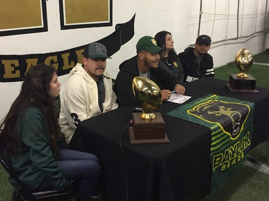 Abilene High running back Abram Smith, center, prepares to sign his national letter of intent to play college football at Baylor while surrounded by family and friends .