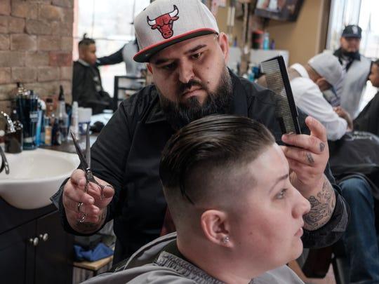Cheeky Chaps manager and master barber Chris Marangos gives Taylor Hall a haircut at Cheeky Chaps Barber Shop in Mesilla.