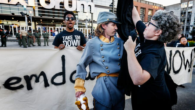 A demonstrator dressed as Confederate Gen. Nathan Bedford Forrest is draped with a black cloth during a #TakeThemDown901 protest in front of the FedExForum before the Grizzlies game in Memphis, Tennessee., Friday, October 13, 2017. Earlier in the day, The Tennessee Historical Commission denied Memphis' request to remove a statue of Forrest from a city park.