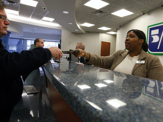 A bank teller assists a customer at Fifth Third's branch on Fountain Square.