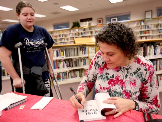 Portland author April Henry signs a copy of one of