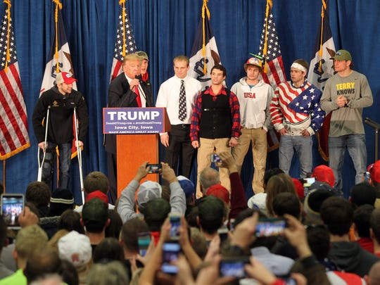 Republican presidential candidate Donald Trump greets members of Iowa's wrestling team at the University of Iowa Field House in Iowa City at 8:31 p.m. Tuesday, Jan. 26, 2016.