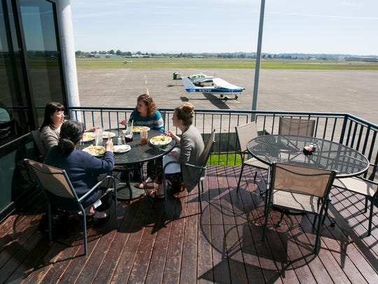 Diners eat lunch on the patio of Flight Deck Restaurant