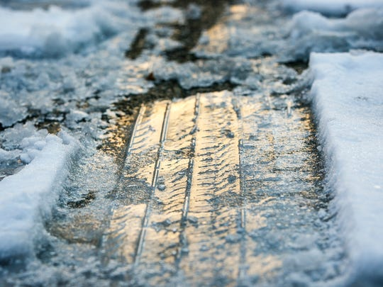 Icy tire treads can be seen in parking lot in Downtown Salem on Friday, Dec. 16, 2016. With the sun shining through the afternoon but temperatures remaining in the low 30s, much of the week's snow melted and then froze into ice.