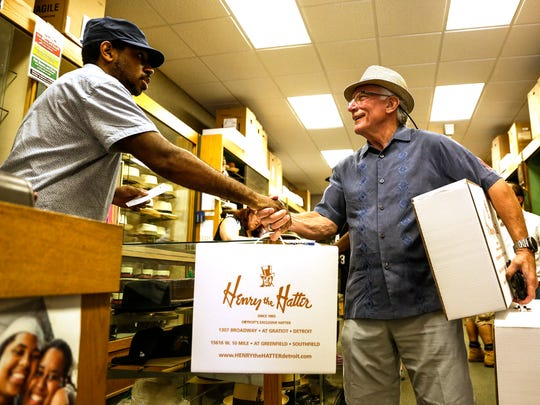 Jovon Garrison, salesperson at Henry the Hatter, shakes hands with Wayne Curto of Shelby Township, a customer at the store on Friday, June 30, 2017 in Detroit.