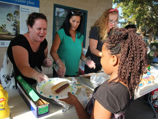 Jessica Brooks passes out hot dogs and hamburgers to