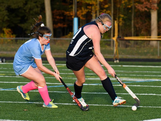 MMU's Catherine Ordway (20) runs past South Burlington's Kate Hall (2) with the ball during the field hockey game between the Mount Mansfield Cougars and the South Burlington Wolves at South Burlington High School on Friday afternoon October 27, 2017 in South Burlington.