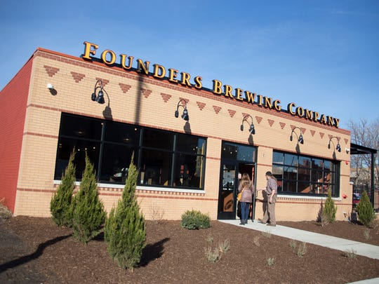 Founders Brewing Co. co-founder Dave Engbers of Grand Rapids opens the door for his wife Amy Engbers at the Detroit taproom on Friday, Dec. 1, 2017.