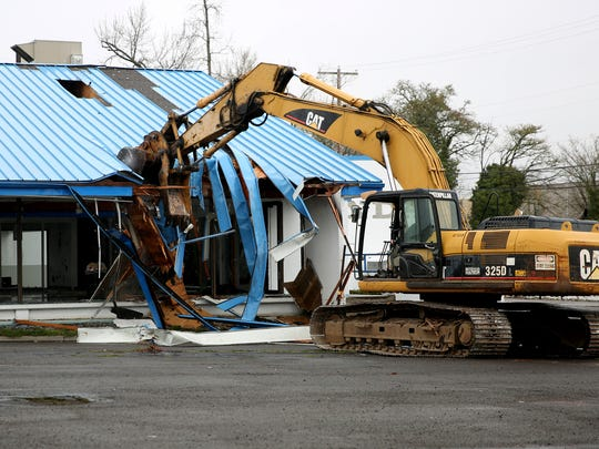 Salem Police Chief Jerry Moore operates an excavator to tear down a building at the former O'Brien Auto Group and the future home of the Salem Police Facility at Division St. NE and Commercial St. NE in Salem on Friday, March 16, 2018.