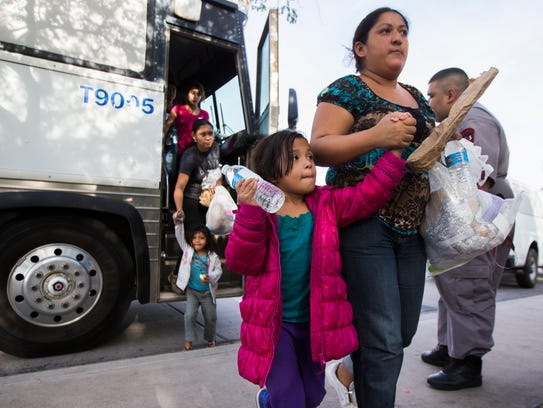 Migrants get off a bus after being released by ICE