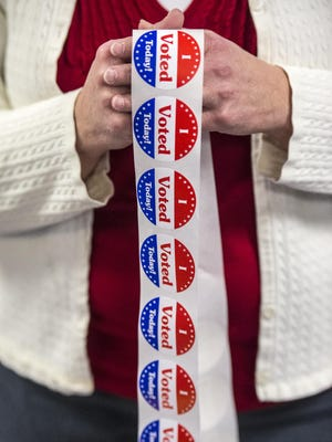 Voters get a sticker after casting their ballots on Town Meeting Day in Colchester on Tuesday, March 3, 2015.