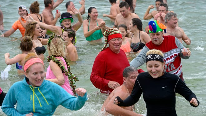 Hundreds hit the Gulf of Mexico for the Polar Bear Dip on Friday at the Flora-Bama to celebrate the first day of 2016 new year. The annual tradition brings out costumed patrons in droves for drinks and a cool dip in the water followed by a traditional feast with black-eyed peas, cornbread, ham and the trimmings.