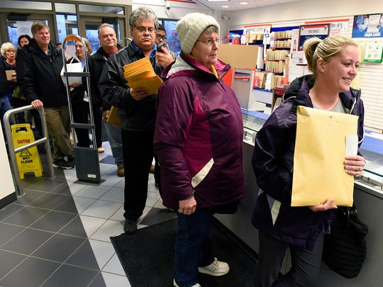 People stand in a growing line to mail packages Monday,