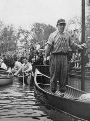 A freshman stands up in a canoe with fans in the stands