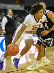 University of Evansville's Dru Smith (12) drives against Missouri State's Ronnie Rousseau III (14) as the University's of Evansville Purple Aces play the Missouri State Bears at the Ford Center Wednesday, January 10, 2018.