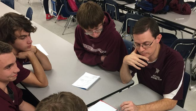 Henderson County High School academic team coach Brian Sullivan works with members of the junior varsity quick recall team between matches at the Junior Varsity Challenge at Apollo High School in Owensboro on Nov. 12. Henderson County placed first in quick recall and first overall at the meet.