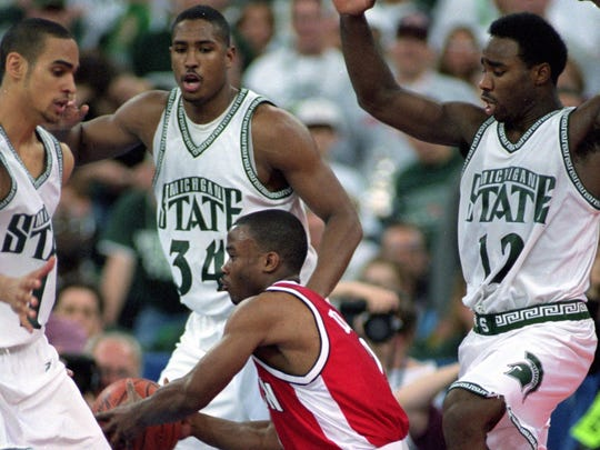 Travon Davis #2 of the Wisconsin Badgers moves to pass the ball as he is guarded by Andre Hutson #34 and Mateen Cleaves #12 of the Michigan State Spartans during the NCAA Men''s Finals Four Game at the RCA Dome in Indianapolis, Indiana. The Spartans defeated the Badgers 53-41.