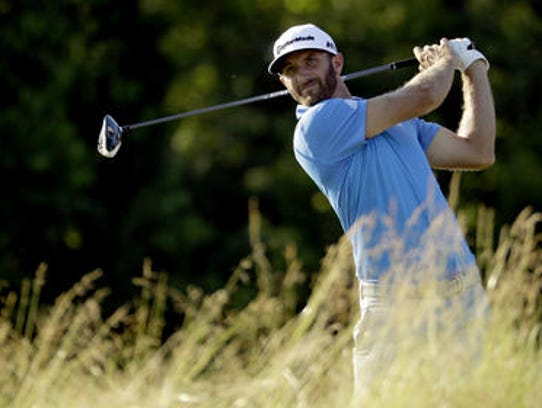 Dustin Johnson watches his tee shot on the fourth hole